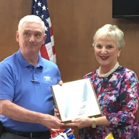Outgoing President Jim Payne receiving a plaque for his service from Sallie Lipsey, incoming President