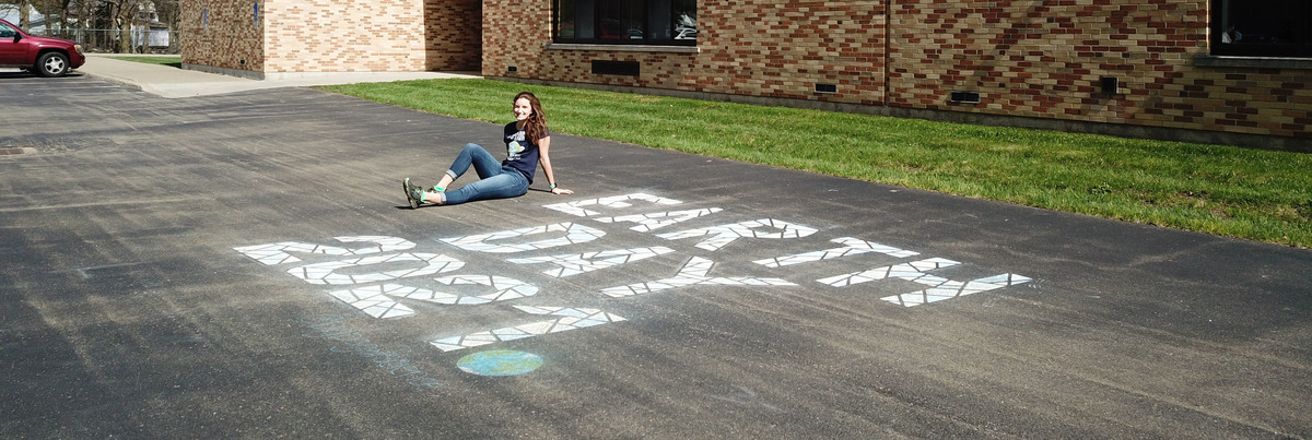 Miss Kreppel poses with her Earth Day chalk drawing