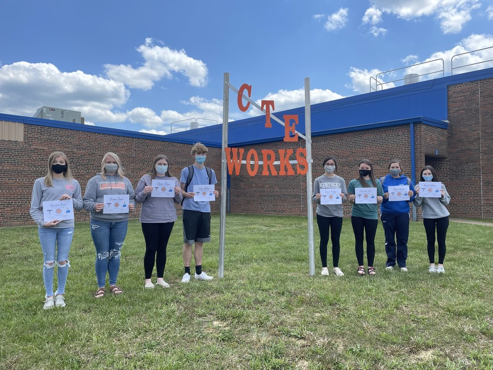 students standing in front of a CTE Works sign holding certificates