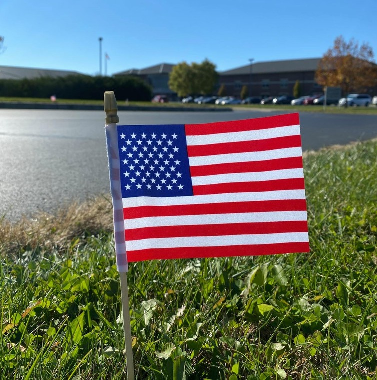 Miniature American Flag stuck in lawn in front of school building