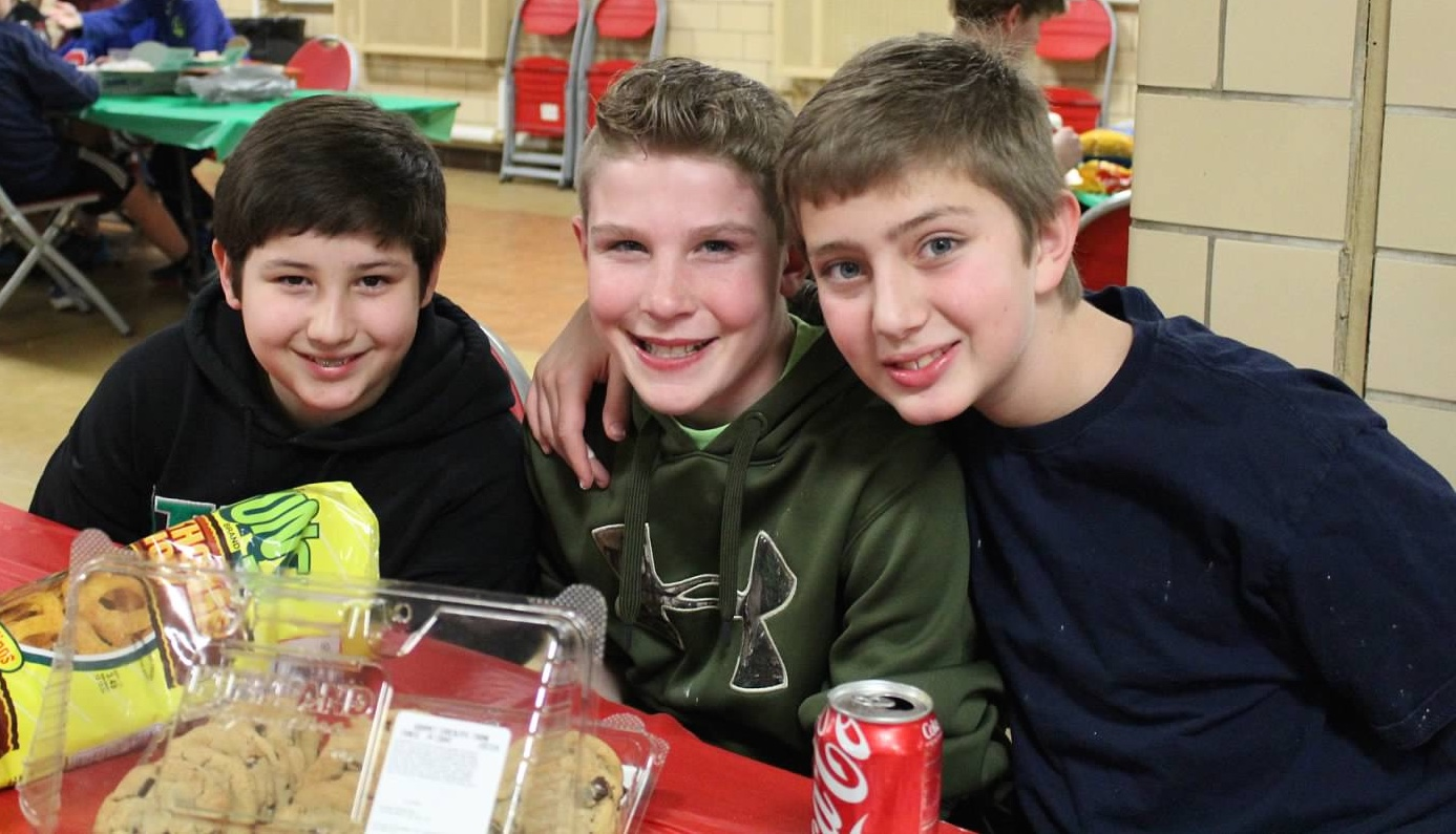 Three 7th graders sitting at a lunch table smiling at the camera