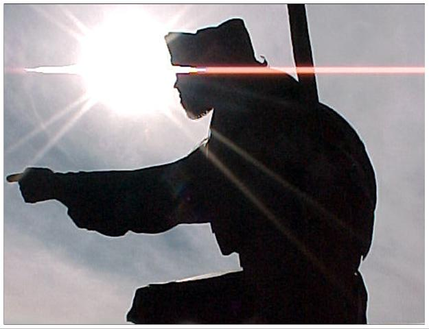 Silhouette of a person or statue against a bright sun