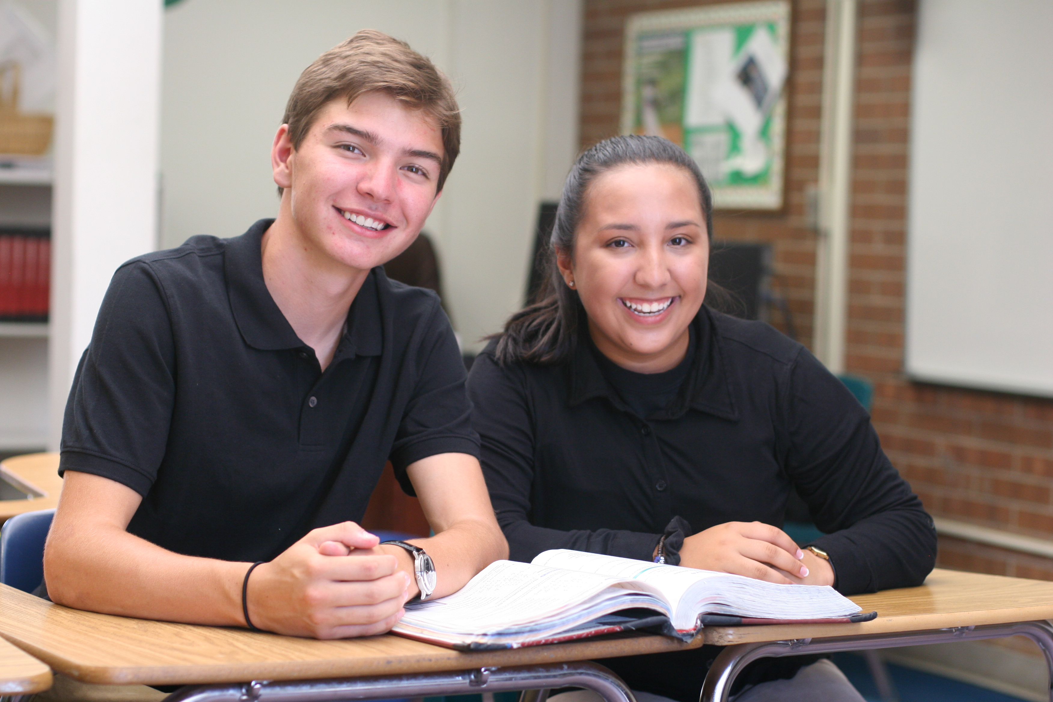 2 students posing at their desk
