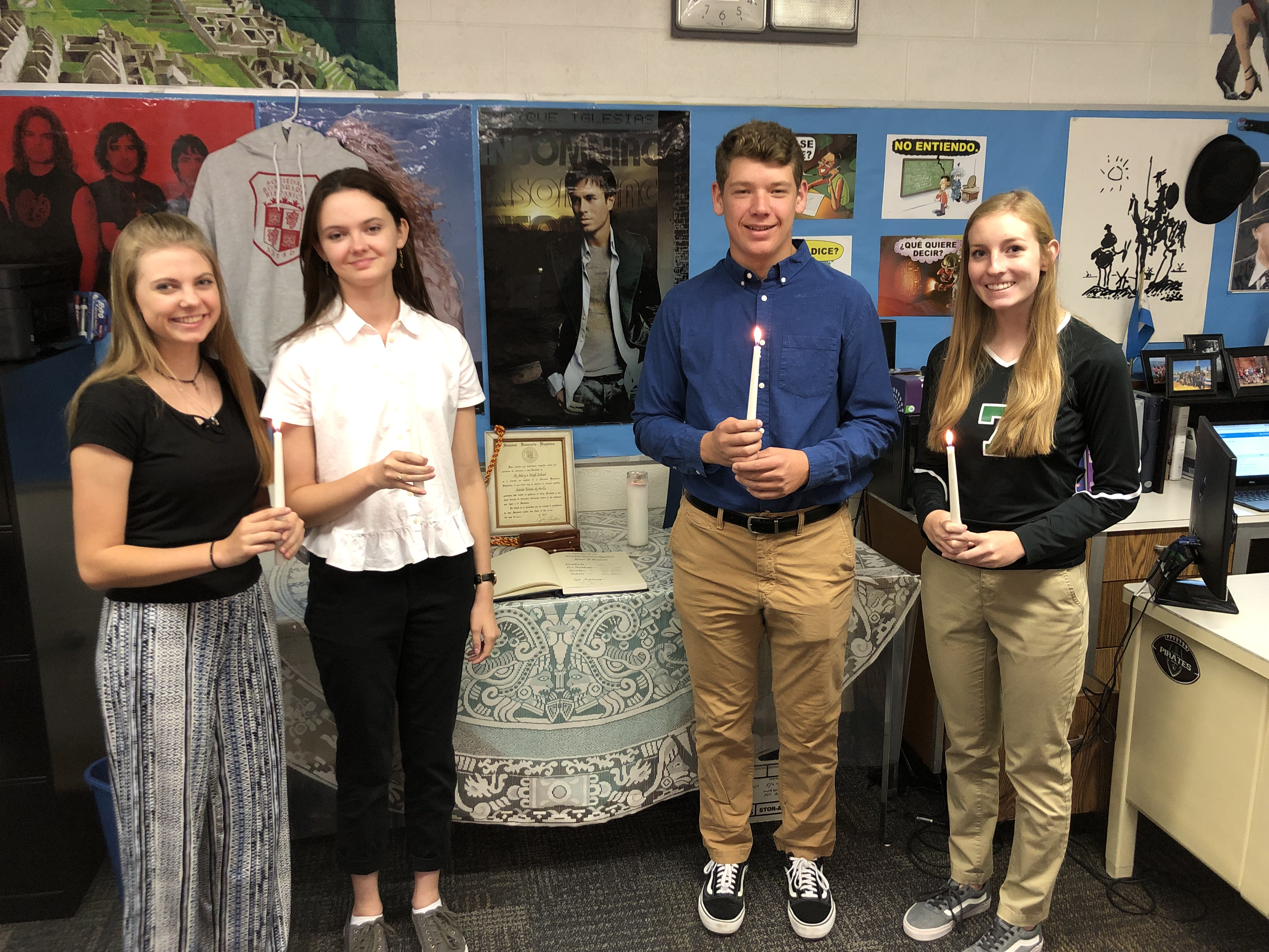4 students holding a candle at an event