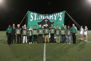 Hall of Fame inductees standing in front of a St. Mary's banner on the football field
