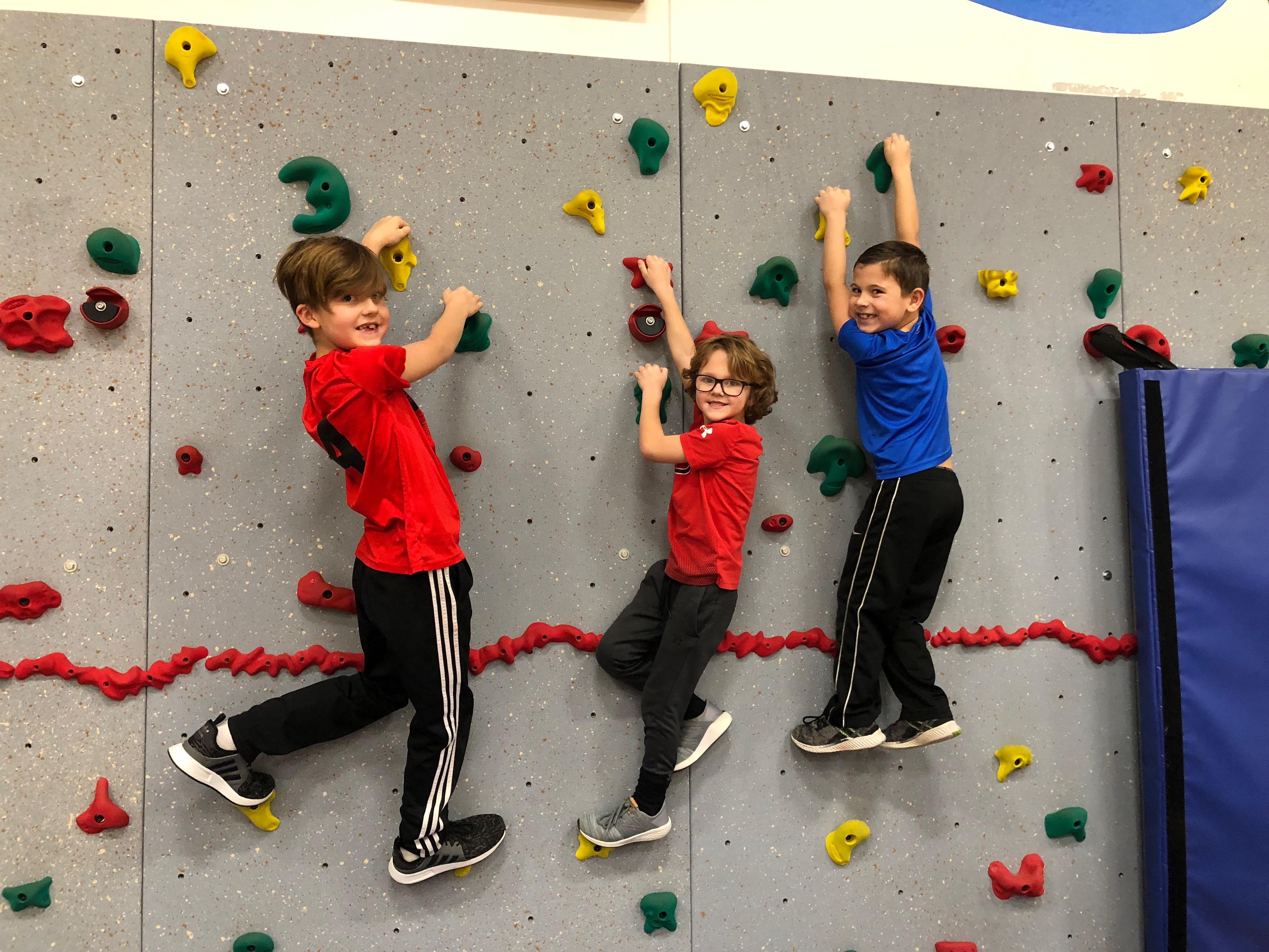 Three students practicing on a mountain climbing wall