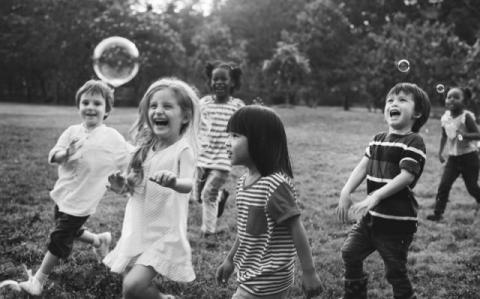 A photo of kids playing with bubbles.