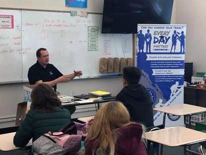 A photo of a teacher explaining to the class.