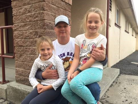A photo of a dad with his 2 daughters.