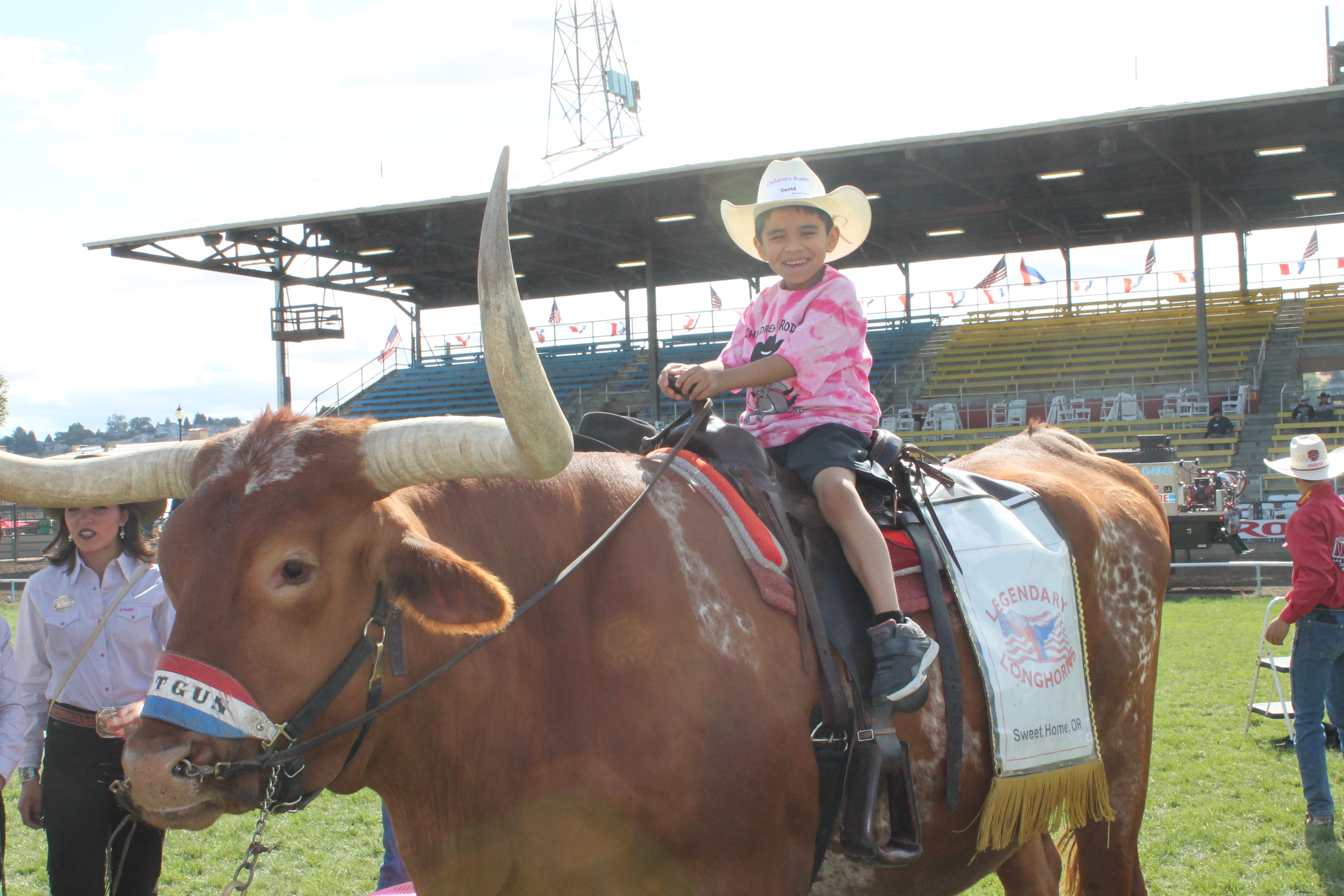 A photo of a kid riding a longhorn.