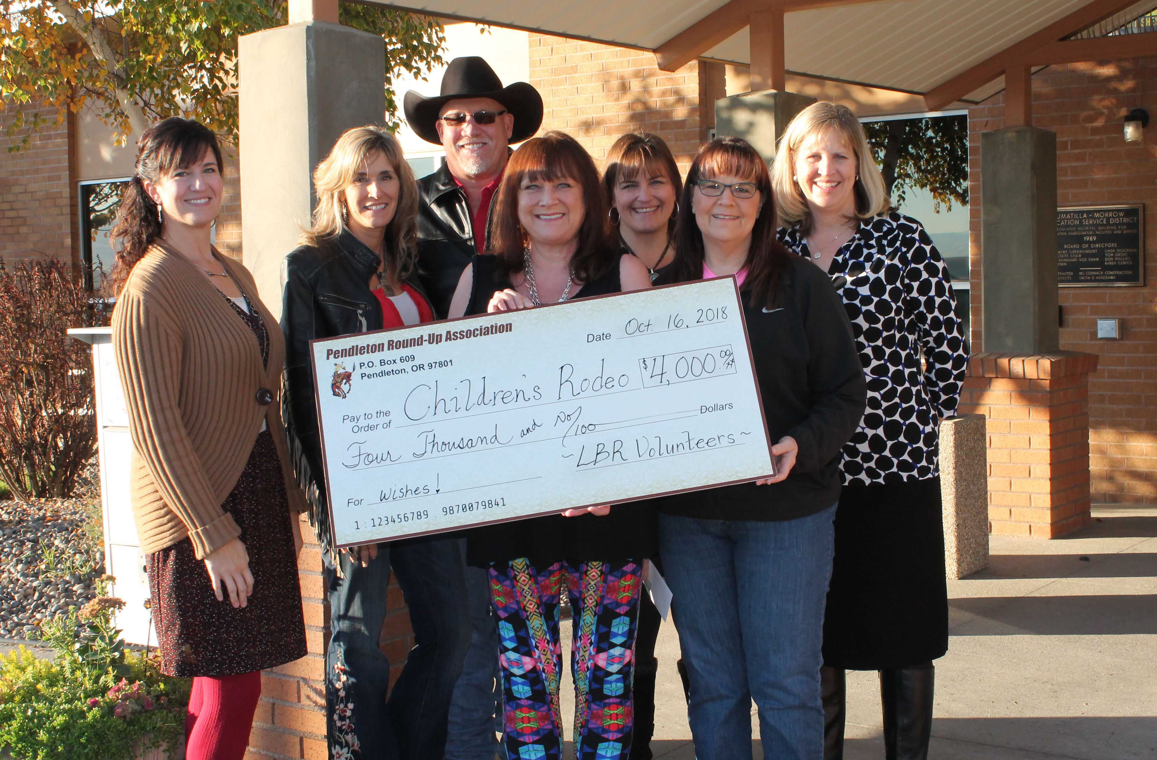 From left, Chrissy Nelson (IMESD), Jill Ledbetter and Mike Ledbetter (Round-Up), Linda Smith, Char Surber, Karen Parker and Michele Madril (all IMESD) pose with the donation check from Let 'er Buck Room volunteers.