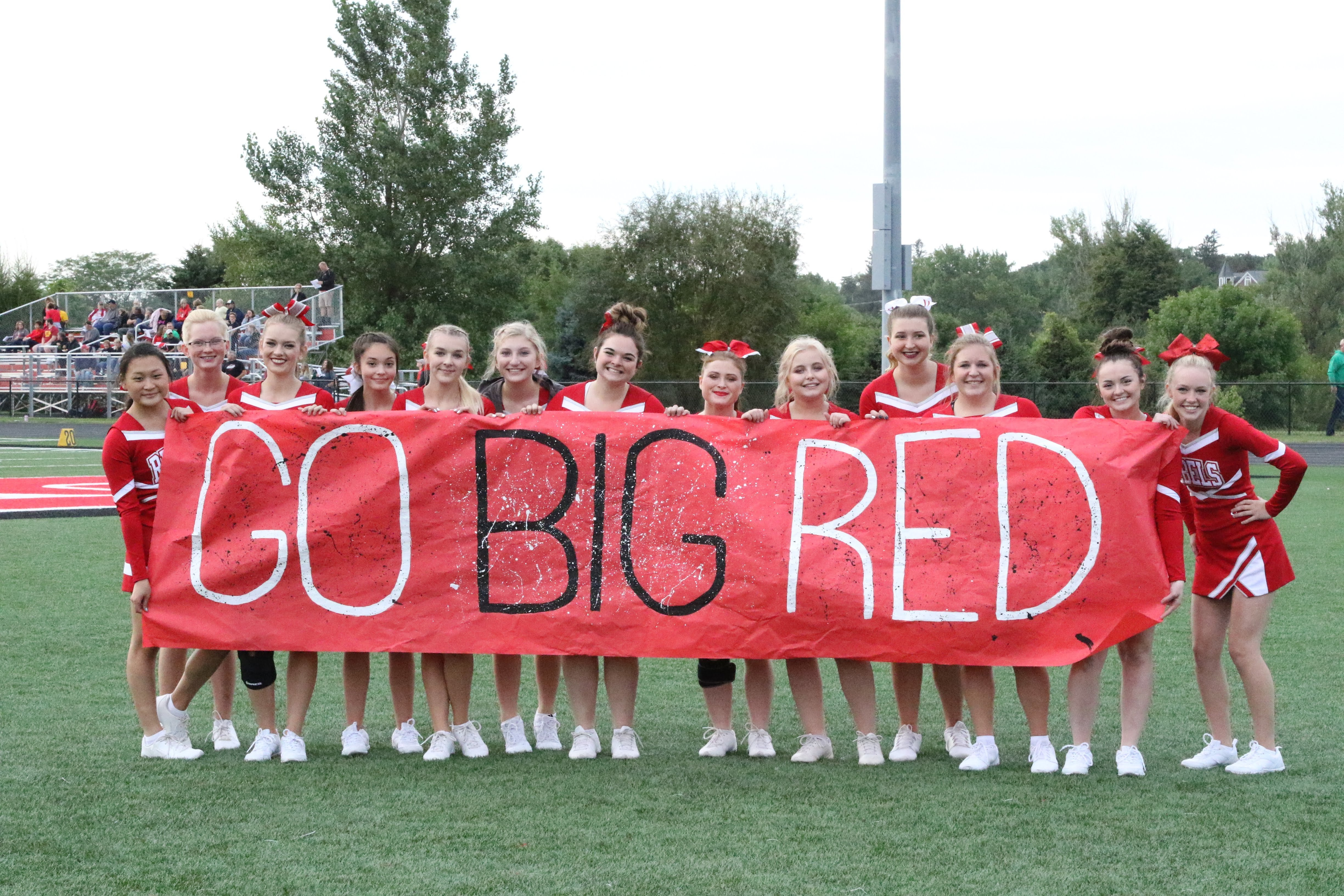 """Cheerleaders with a """"Go Big Red"""" sign"""