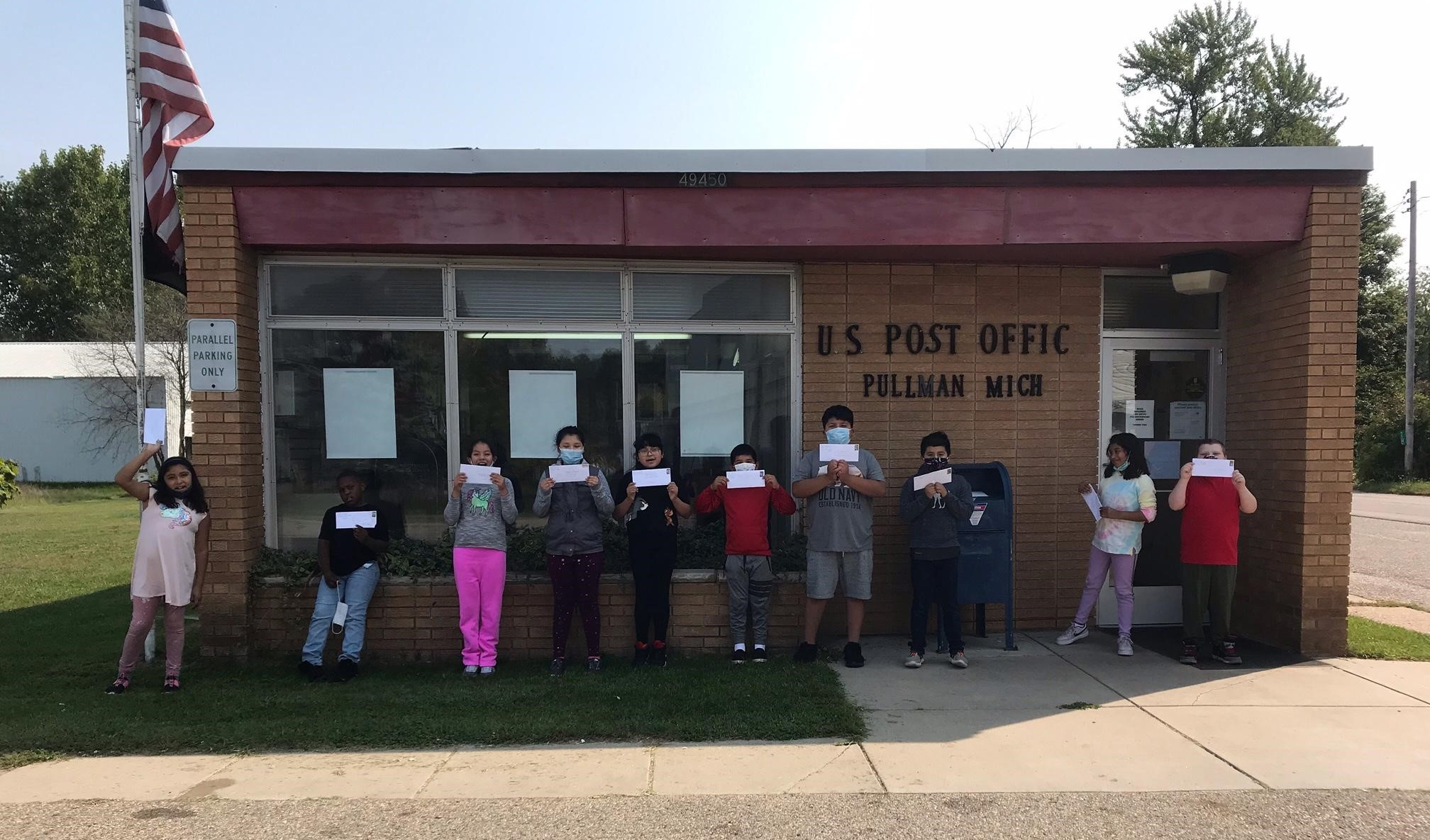 Students holding up letters to mail at the post office.