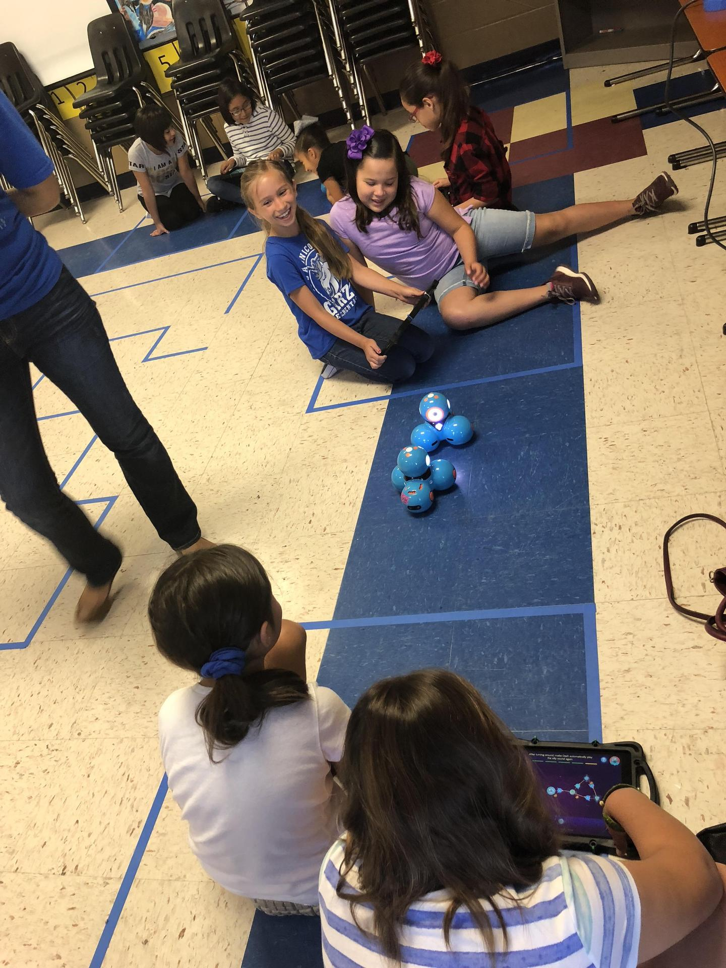 Students working with small robots on the floor