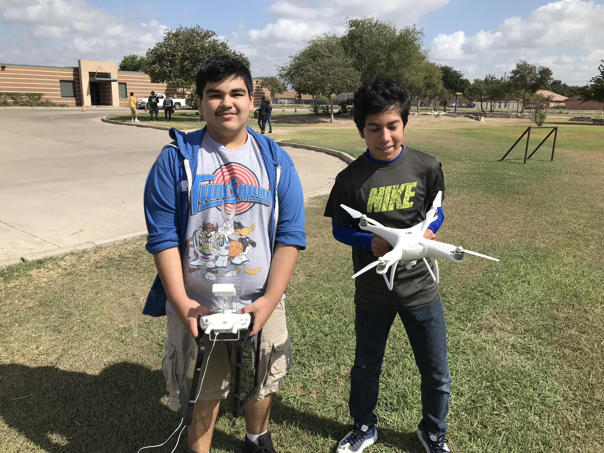 Students standing outside holding a drone