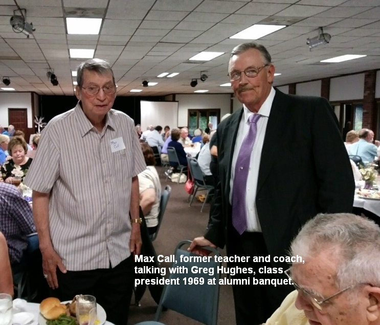 Max Call, former teacher and coach, talking with Greg Hughes, class president 1969 at alumni banquet