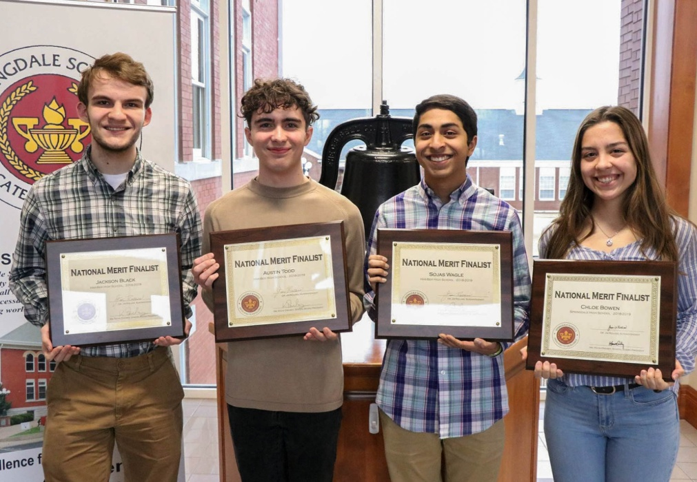 A photo of students with award plaques