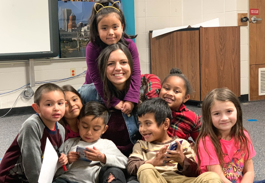 A photo of a teacher with several students smiling