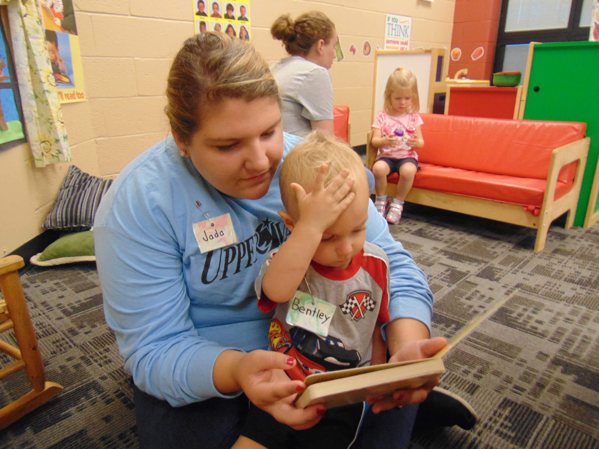 High School student teacher with young preschool student reading a book