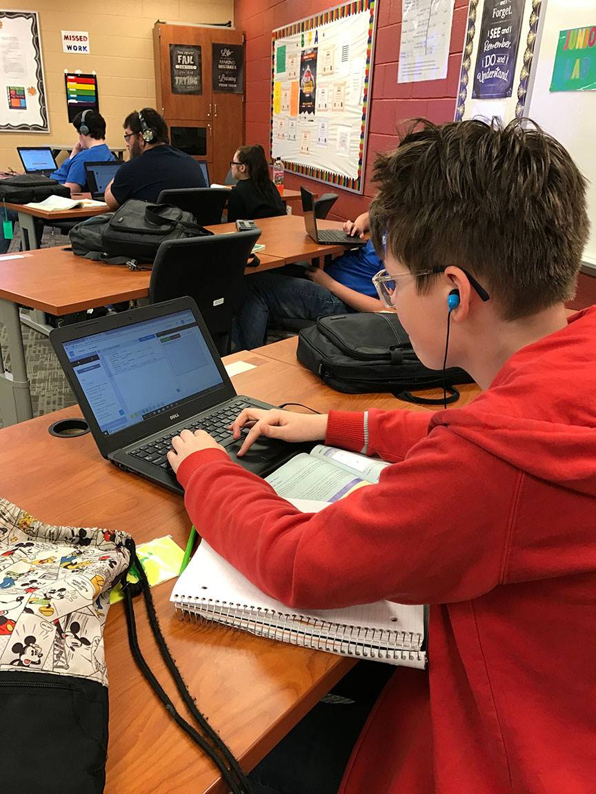 Student working on computer with earbuds in