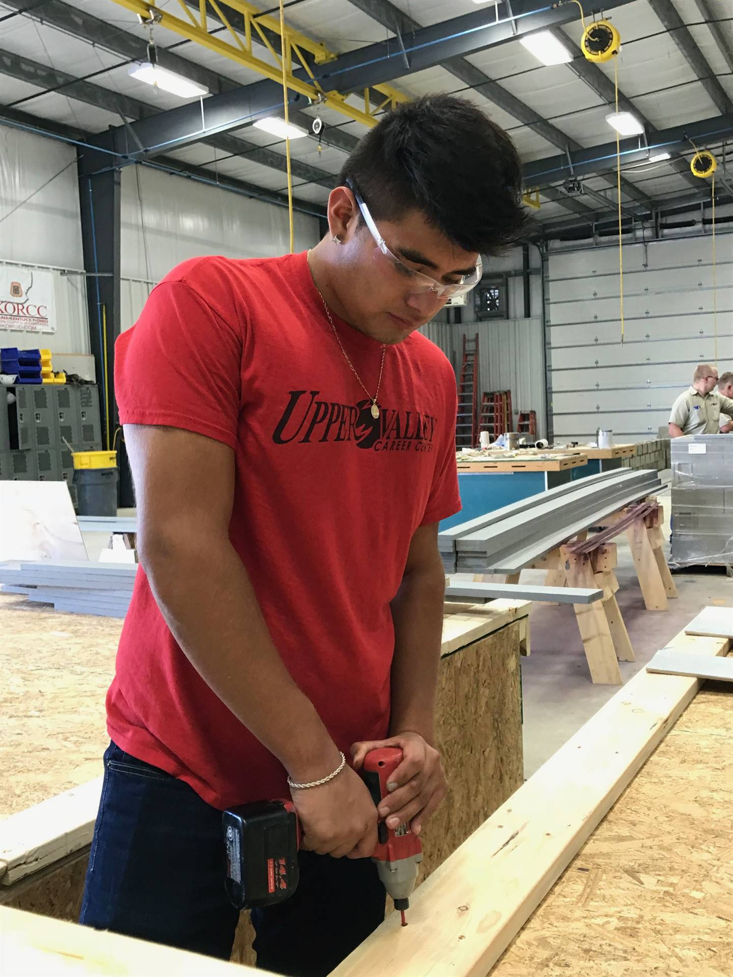 Student drilling nails in wood