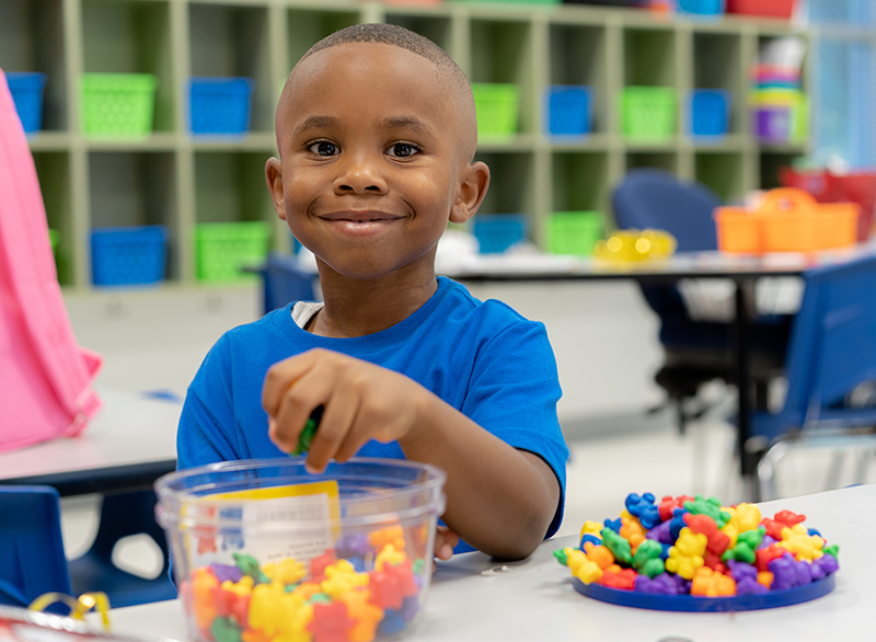 young African American boy pulling colored toys out of a container