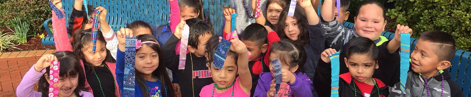 young children of various ethnicities holding pieces of ribbon in the air