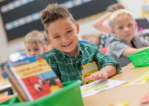 kindergarten age male student, hair spiked up, wearing a green shirt and sitting at a desk
