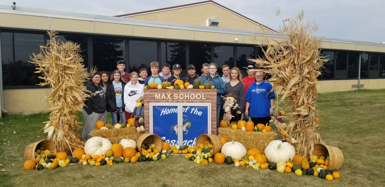 FFA members in front of the school sign decorated for fall.