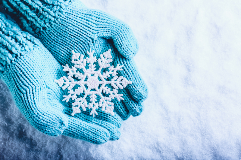 Photo of blue mittens holding a snowflake