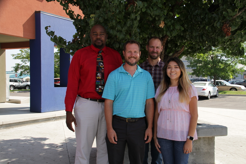 The IT team standing in front of a tree