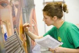 a student painting on a wall