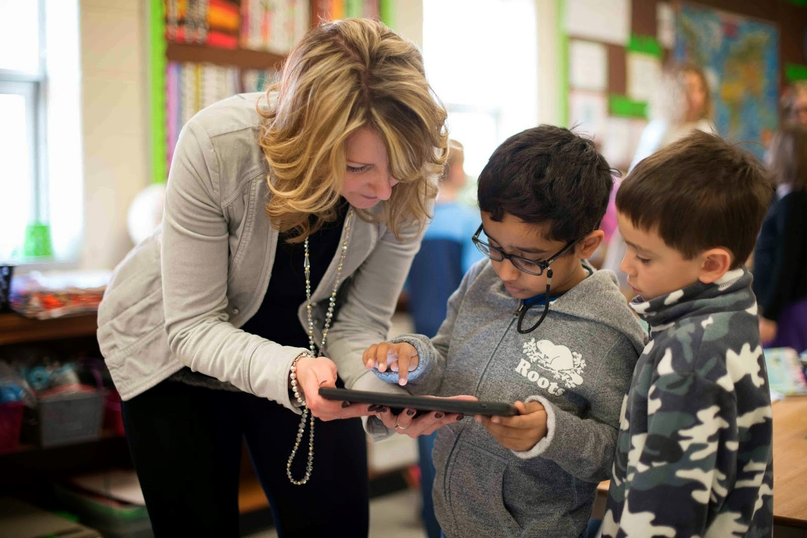 a teacher working with kids on a tablet