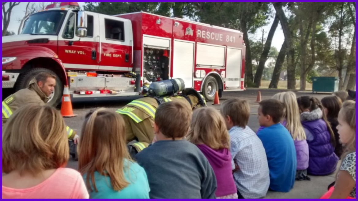 kids talking to a firefighter in front of a fire truck