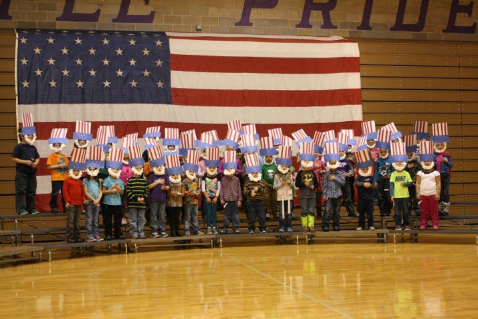 kids standing in front of a big American flag