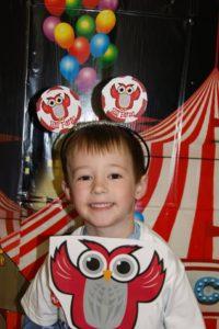 Little boy holding paper owl cutout