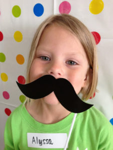 Little girl with paper moustache