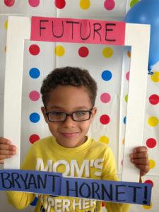 """Little Boy holding """"Future Bryant Hornet"""" frame"""