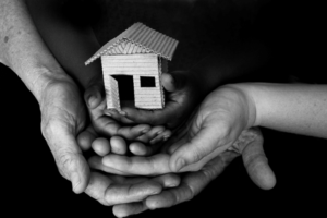 Black and white photo of hands holding a birdhouse