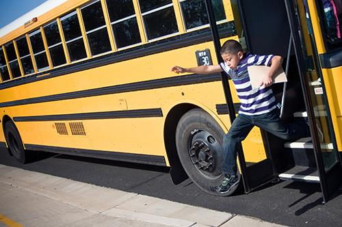 Photo of a student going down a school bus.