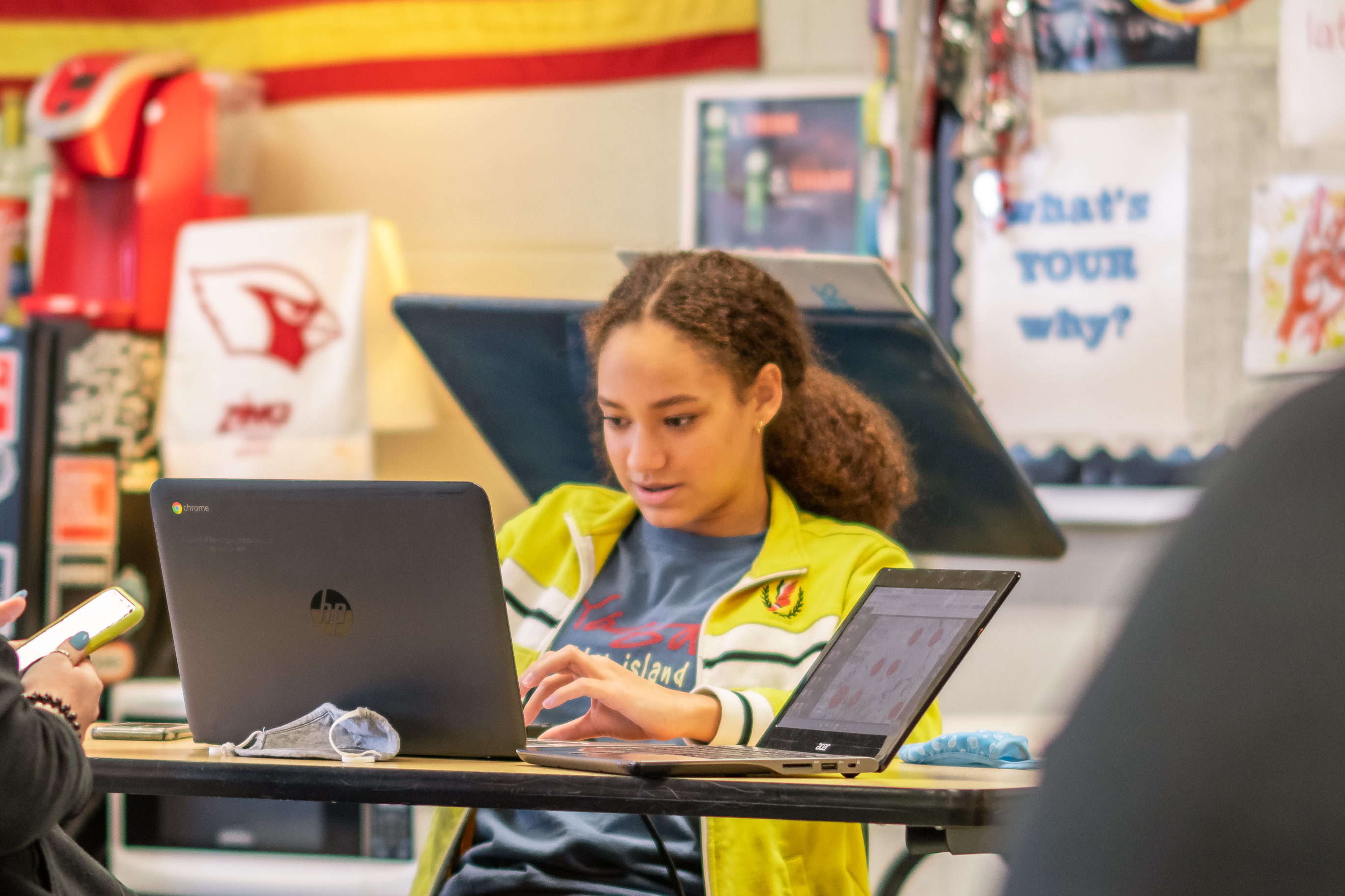 Student sitting at a classroom desk, working on her Chromebook.
