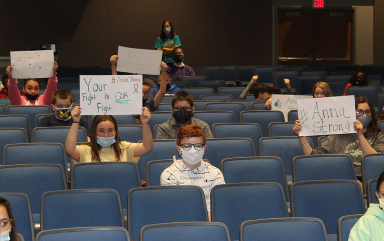students in auditorium masks holding up signs