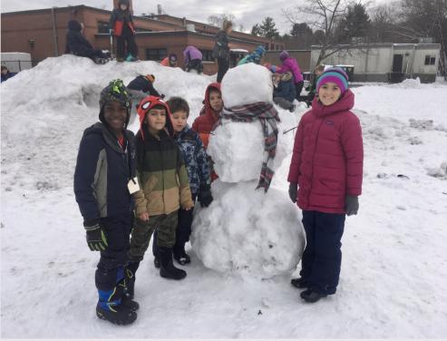 Students building a snowman
