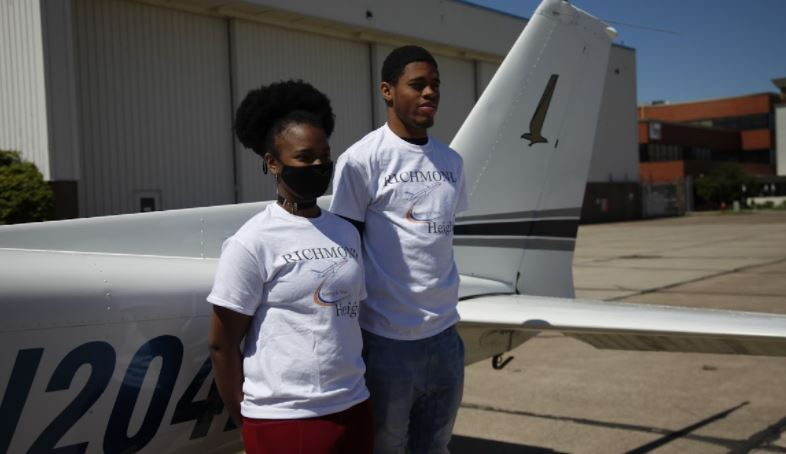 image of students standing next to a plane