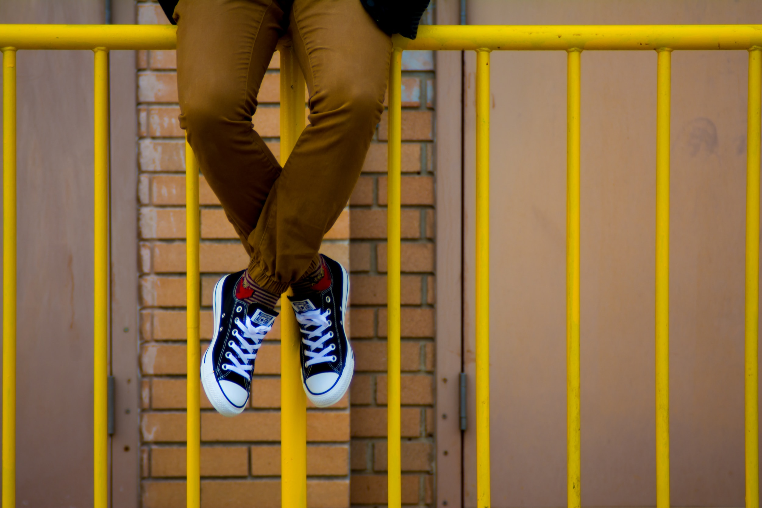A student sits on a yellow railing.