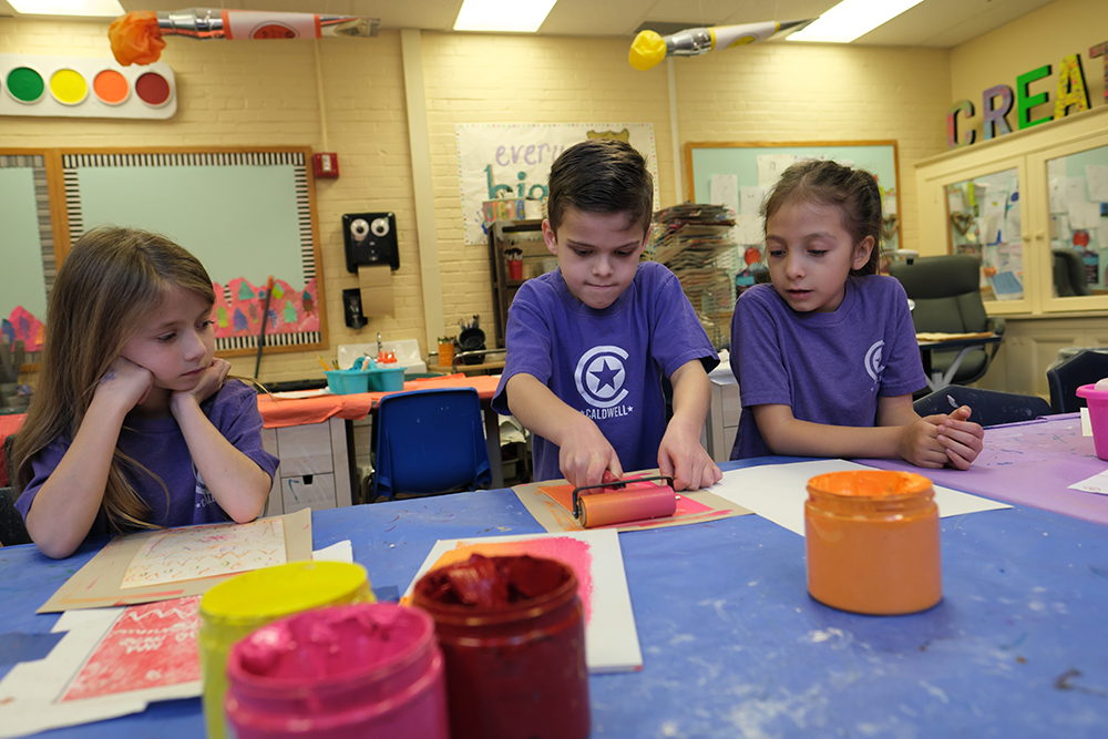 elementary age boy with dark hair and a purple shirt on rolling paint on paper. Two girls wearing purple shirts are watching him. Paint containers are on the art table, red, pink, yellow and orange.