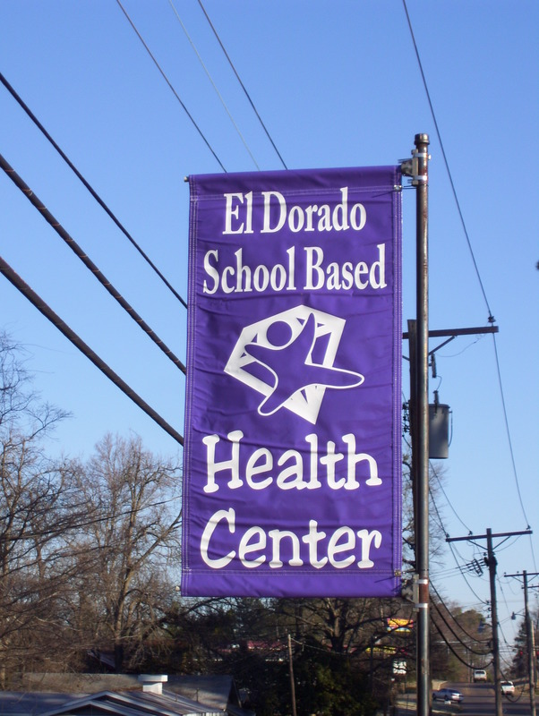 A photo of a El Dorado School Based Health Center banner hanging on a street.