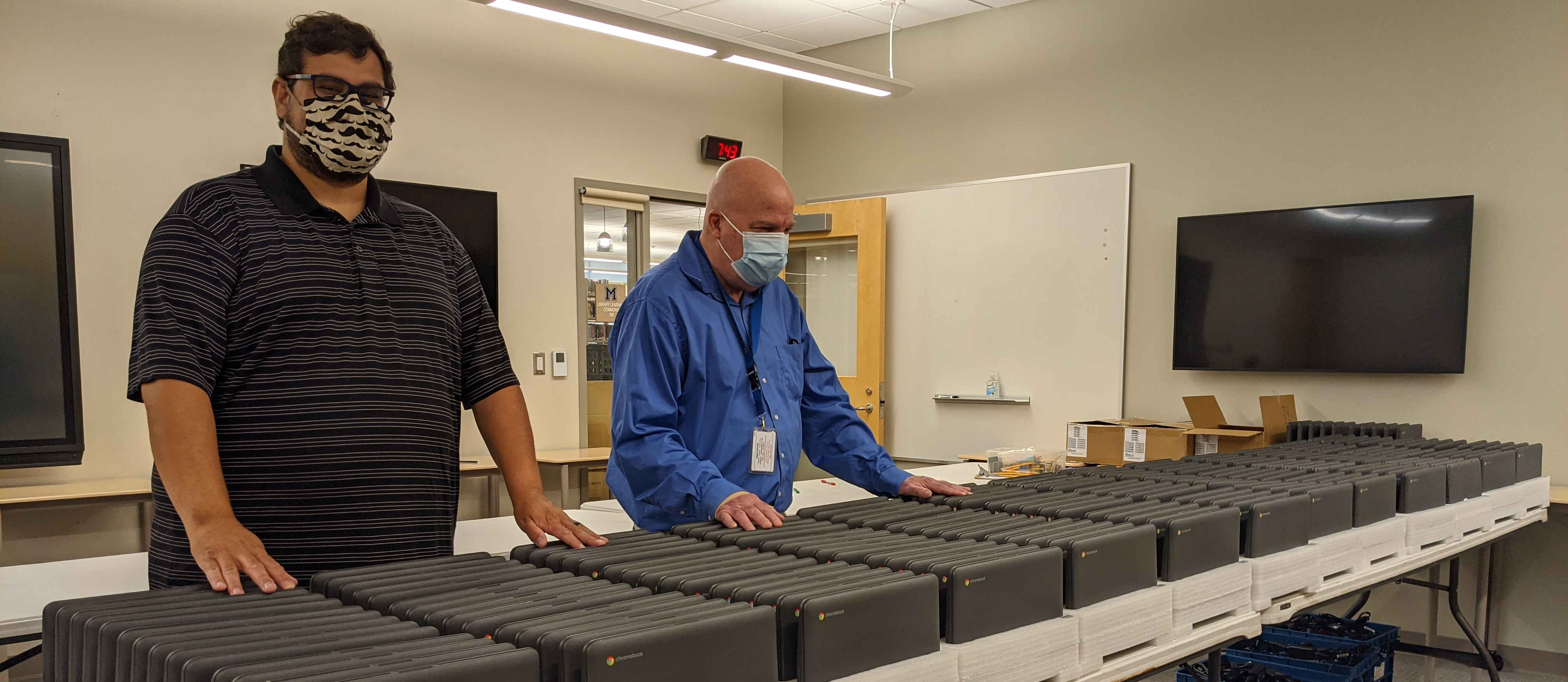 Staff members stand behind hundreds of chromebooks ready to deploy to students