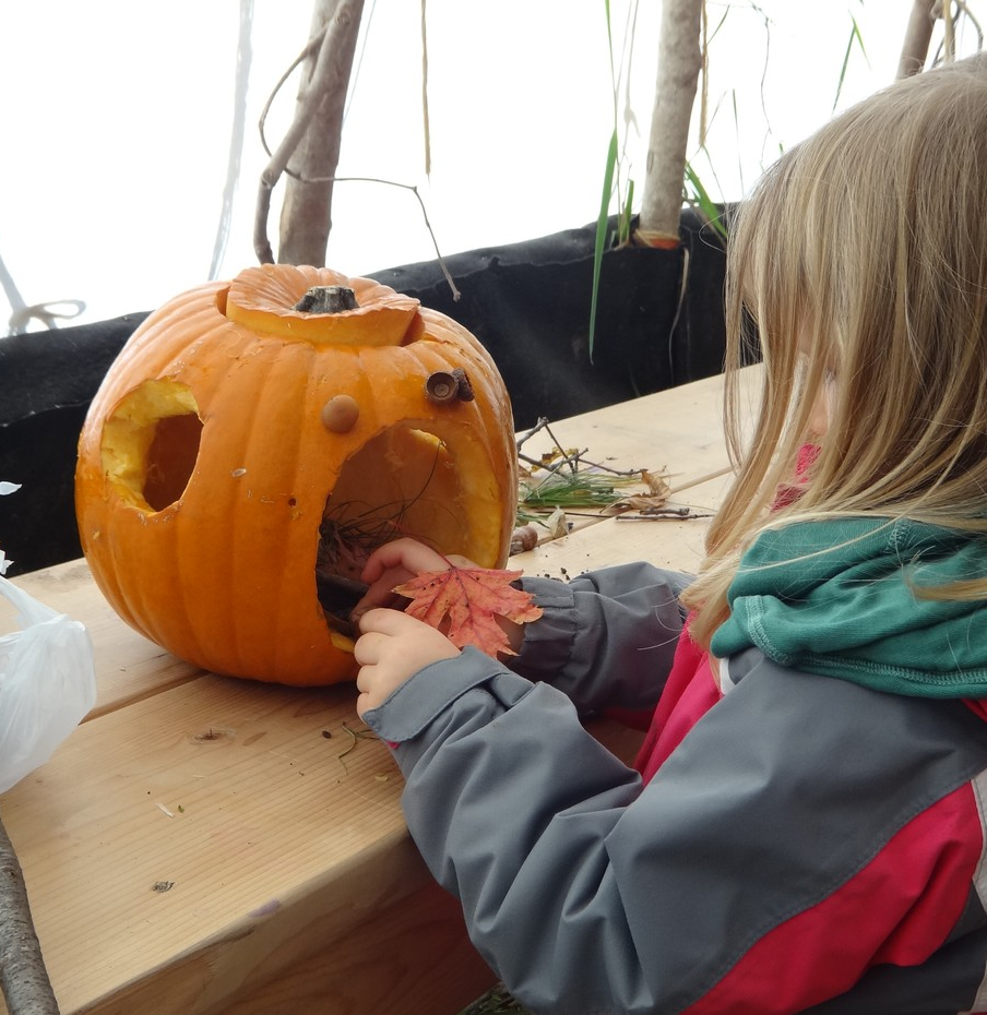 child crafting with a pumpkin