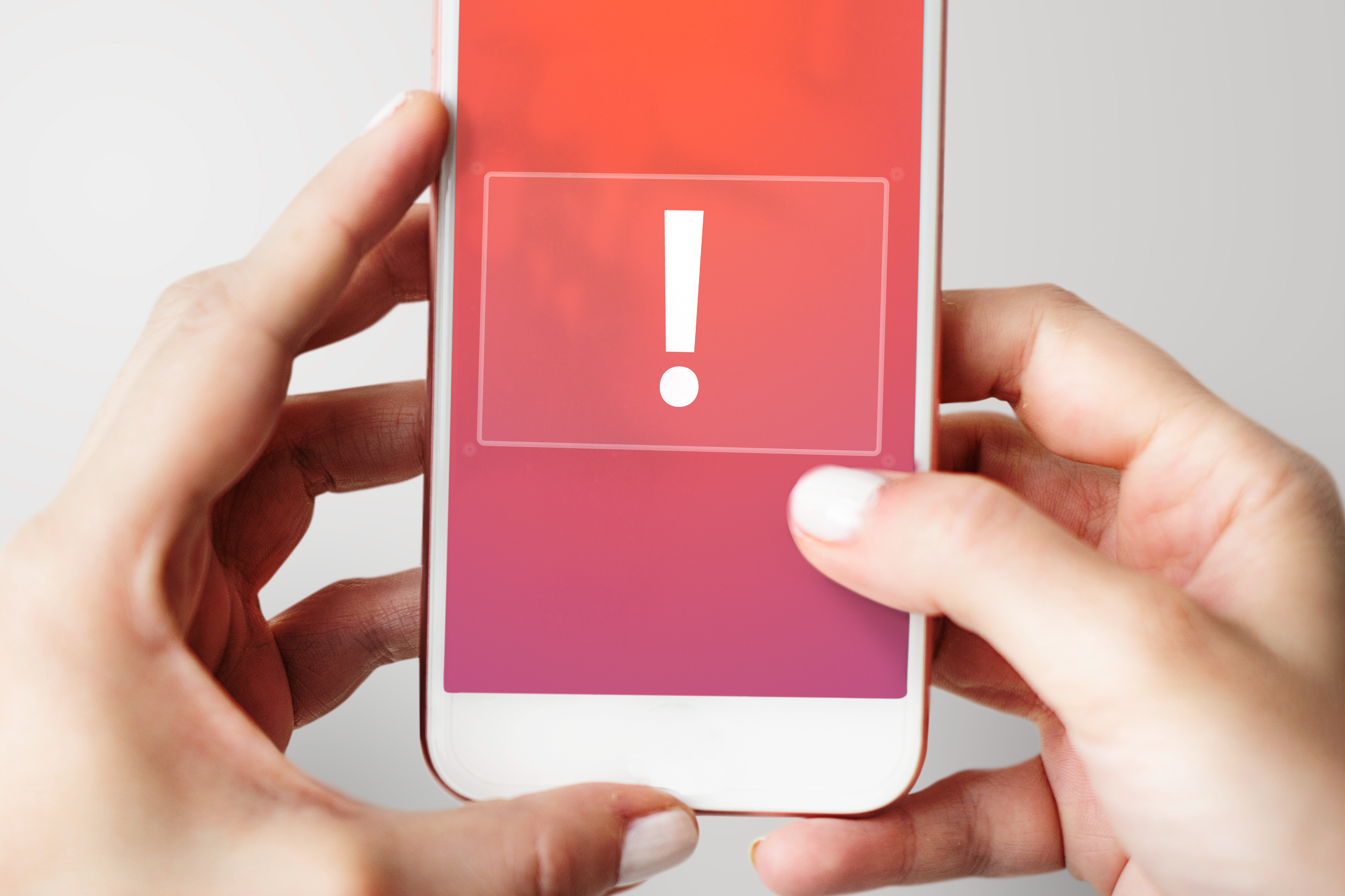 Hands holding a cell phone with an exclamation point on the screen for a message